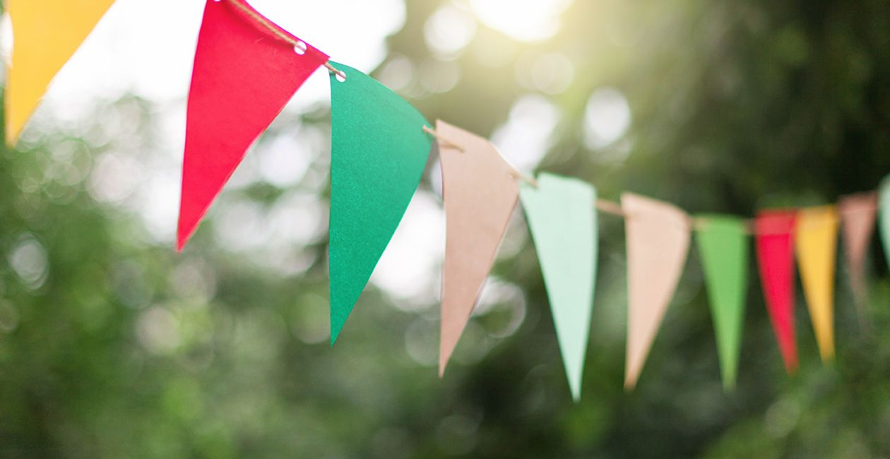 Colorful flags at sunset in garden. Concept of celebration or party. Paper festive decoration outdoor.