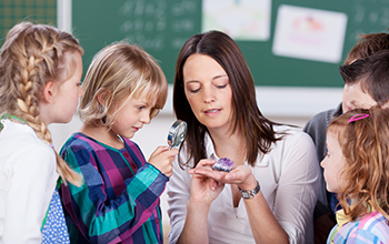 Kids gathered around teacher holding a geode with the boy next to her looking through magnifying glass