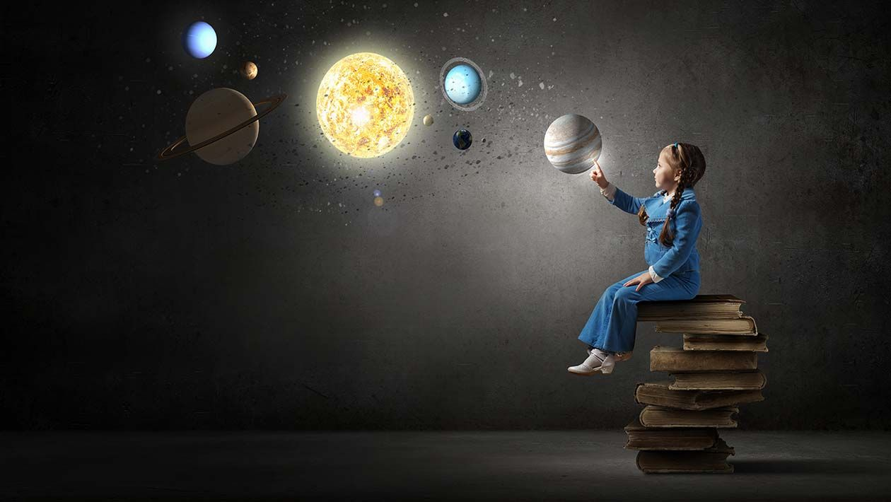 A girl sitting on a stack of books point to planets in the air