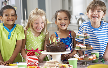 Kids around a table with a chocolate birthday cake with candles, a tray of cupcakes and wrapped present